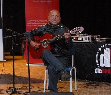 Mit Gitarre auf der Bühne sitzend - Foto: © 2013 by Schattenblick